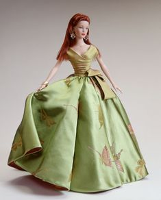 Papillion (2002) DRESSED DOLL  TW 1202  LE 2000  $149.99  (Rust red hair; blue eyes; original arms)     For the Grand Launch Ball of the Cosmetics Campaign, Tyler Wentworth® envisioned a gown that embodied the quintessential elements of one dramatic seasonal vision.  To accomplish this, Tyler designed a new silk jacquard that would capture the innocence of spring with larger-than-life iridescent butterflies against the freshness of green to anchor a fitted and draped bodice of silk shantung.