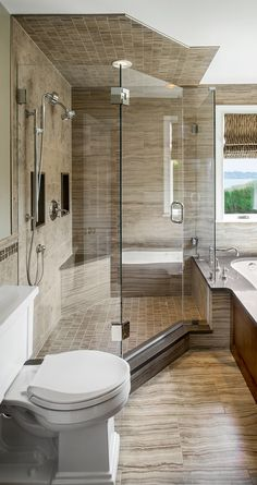 The borders of the shower niches are made from the same stone as the sill and the shower was delicately fit into the available space of this condo master bathroom. | Red House #masterbathroom
