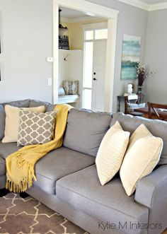 How to make a gray paint colour feel warm. Shown in living room with Revere Pewter, gray sectional and yellow and blue accents and home decor by Kylie M Interiors