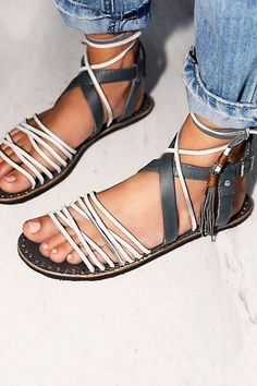 Strappy leather flat sandals. Tasseled lace up ankle closures. Studded footbed accents. Style #: OB482741 Material: Leather Color: Smoke Sizes are in European sizes, please see shoe chart below for si