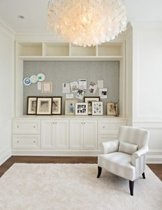 Bedroom sitting area with cut out area between top and bottom shelves with plush, white square rug and small white and grey striped chair and large white flower petal ceiling light
