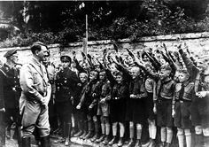 Adolf Hitler with Hitler youth, undated, arms raised in Nazi salute
