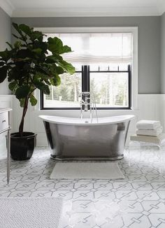 Exquisite bathroom boasts a white rug placed on white and gray mosaic floor tiles at the foot of a modern cast iron bathtub flanked by a lucite bench and a fiddle leaf fig place. Bathroom Rugs, Small Bathroom, Master Bathroom, Bathroom Ideas, Bath Ideas, Bathroom Inspiration, Grey Slate Bathroom, Kitchen And Bath Design, Modern Shower