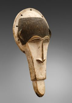 AN IBO ZOOMORPHIC MASK  Nigeria  Of elongated form, the blackened forehead with carved parallel grooves, long flat nose over simiesque snout, painted white and black.  34 cm. high