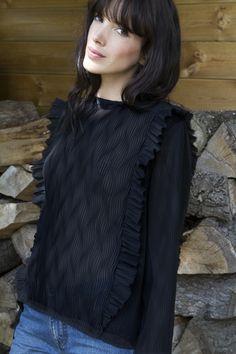 """Originale et féminine Marguerite se décline en noir dans <strong>un tissu plissé</strong>. Votre blouse Marguerite donnera de l'allure à vos tenues. Les finitions pour cette blouse sont des volants à <strong>bords francs</strong>. Votre blouse Marguerite existe en <a title=""""Boots marguerite safran"""" href=""""http://www.balzac-paris.fr/produit/blouse-marguerite-moutarde/"""" target=""""_blank"""">safran</a>. • Votre blouse Marguerite se resserre légèrement dans le bas • Col rond • Volants devant e..."""