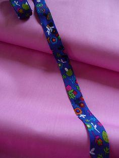 Super süßes Schrägband mit Blumen und Pilzen.  Das Schrägband ist blau und die Blumen und Pilze sind Rot, Blau, Weiß, Grün, Orange, Rosa. Eine Blume ist  ca. 2 cm hoch und ca. 1 cm breit, Das Schrägband ist ca. 2 cm breit. Das Schrägband ist gefalst. Man braucht es nur noch zusammen zu klappen. Der Preis versteht sich für 2 m. Die einzelnen Stücke sind immer nur 2 m lang.