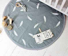 Beautiful modern playmat in a colour scheme of white feathers handprinted on grey base fabric. Please note as each is hand printed and hand made to