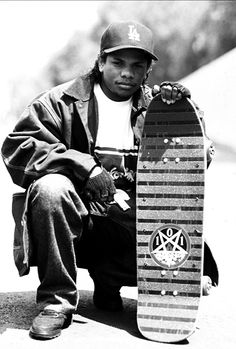 "Eazy-E poses with a Natas Kaupas ""Devil Worship"" model skateboard and a handgun. In 1993 this was the coolest thing imaginable."