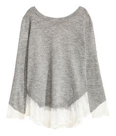 Graumeliert. Pullover aus weichem Feinstrick. Der Pullover hat einen tiefen V-Ausschnitt im Rücken mit Bändchen im Nacken. Lange, asymmetrische Ärmel mit