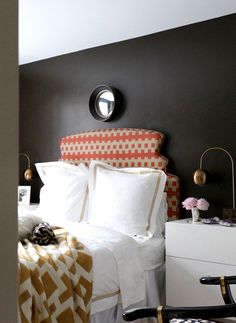 Black bedroom with colorful headboard and white bedding