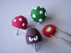 3 Super Mario Bros. push pins and 1 paperclip  by bearduck: One power up mushroom push pin, one 1up mushroom push pin, one goomba push pin, one fire flower paper clip. #Pushpin #Mario_Brothers