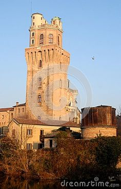 Photo made at the tower of the Observatory of Padua in Veneto (Italy). In the image you can see the tower of the former observatory of Padua also called devil's tower lit by the afternoon sun, photographed from the south west that allows you to see part of the buildings that are at the base and near the faculties of astronomy, which towering high in the blue sky.