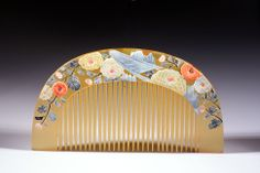 Japanese comb decorated with impressive flower motifs. Mother-of-pearl and coral are inlaid or stuck in relief for a better effect.