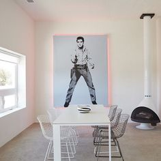The 1200-square-foot home is filled with reworked pieces including the Elvis artwork she embellished with pink lights fabricated by the Neon Gallery in Houston and the refurbished Bertoia chairs from Cast Crew. The minimal color palette is echoed in the freestanding Malm fireplace and the concrete floor sculptures by William Vizcarra from Wrong Marfa. Photo: Christopher Sturman @sturman70 / #dwell #marfa #elvis