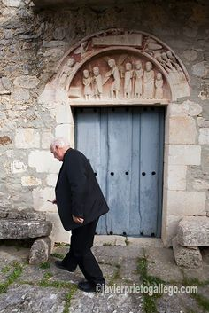 El párroco Bernardino Ortiz ante la puerta y tímpano de la iglesia de El Vigo. Su representación de El Calvario la hace única. Año 1996. Localidad de El Vigo. Valle de Mena. Merindades. Burgos. Castilla y León. España. © Javier Prieto Gallego; Beautiful Places In Spain, Tourist Spots, Medieval Art, Wanderlust, House, Temples, Abandoned Churches, Spain, Travel Sights