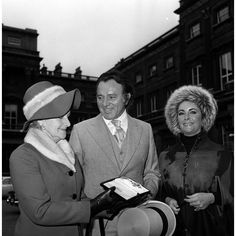 10 November 1970: Richard Burton receives his Birthday Honours award of Commander of the Order of the British Empire at Buckingham Palace. with wife, Elizabeth Taylor,  and sister, Mrs Cecilia James