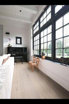 Woonkamer - houten vloer - zwarte kozijnen - witte muren