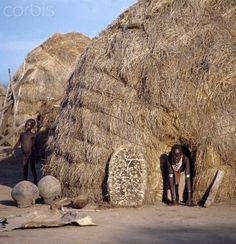 A Karo girl has to almost kneel to come out of the small doorway of her family's high-domed thatched house at Duss. The 'door' of the house is propped up nearby.  Omo Valley, Ethiopia | © Nigel Pavitt