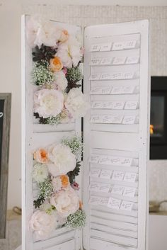 Old shutters with fresh flowers on one side and escort cards on the other.