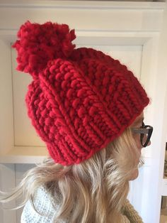This fun, chunky knit hat with a pom pom is just that FUN! Made to order in the color of your choice. For every hat sold, one infant red knit hat will be donated to The American Heart Associations Little Hats, Big Hearts project, providing little ones with a warm, red knit hat. (photo