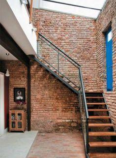 No trecho entre o estúdio e a parede frontal fica o novo hall de entrada, com pé-direito alto e cobertura de vidro. Os tijolos originais das paredes foram descascados e o piso tem peças de demolição que se unem ao cimento queimado.