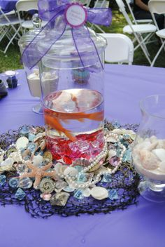 Netting, shells and treasure table decor. Mermsid party center piece with live fish