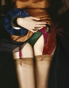 colors - photo by Coppi Barbieri; Skirt and feather bracelet by Louis Vuitton. Garter belt, briefs, stockings by Agent Provocateur. Ring, brooch, feather by Boucheron.