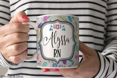 "Personalized Nurse RN Coffee Mug - Custom Nurse RN Ceramic Mug 11oz or 15 oz - SKU-N0001. A ""Personalized Nurse RN Mug - Personalized with your First Name & RN title"" in your choice of 11 oz. or 15 oz. sizes. Premium White Ceramic Mug accented with vibrant, colorful florals on gray background and black text name. Design is printed on BOTH sides of mug and comes in font and color shown. Each mug is made-to-order. SKU: N0001 [ MUG FEATURES ] • High-quality ceramic white mugs, sturdy…"