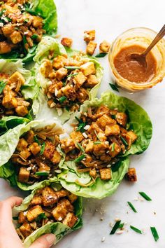 HELLO YUM. Firecracker Lettuce Wraps that are happily vegan - with crispy tofu bits, saucy brown rice noodles, and a creamy sesame sauce. #lettucewrap #vegan #tofu #veganlettucewrap #meatless #vegetarian | pinchofyum.com