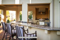 Outdoor kitchen with granite countertops stucco walls, grilling area and bar seating.