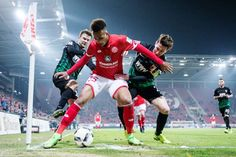Jean-Philippe Gbamin of Mainz is challenged by Paul Verhaegh and Daniel Baier, left of Augsburg during the Bundesliga match between 1. FSV Mainz 05 and FC Augsburg at Opel Arena on Friday in Mainz, Germany.