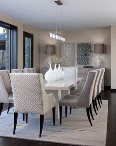 une table design blanche et des chaises rembourrées gris clair