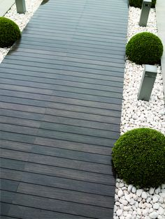 Wooden decking pathway borders by pale gravel/decorative chipping topiary balls and post lighting #rockgardenbordersdecks (rock garden borders decks)