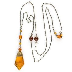Vintage Art Deco lavaliere necklace of brass chain and amber glass. necklace circumference is 36 inches and lavaliere of beads and press molded glass pendant is 4 inches in length. Excellent condition. The pendant has no chips or cracks.