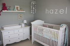 White, classic, and curvy nursery furniture and a handmade paper butterfly chandelier give this nursery a shabby chic flair. The gray walls bring in a muted, modern touch that contrasts well with the patterned crib bedding, while little knickknacks on the high shelf above the changing area add personal touches to this cute baby room. Source: Daffodil Designs