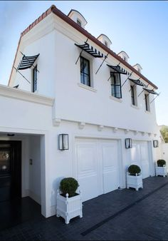 The Urban Electric Company's Vic on Bracket lantern, available in gas and electric, adds a subtle accent to this crisp white exterior. Design by White Stucco House, White Houses, Garage Lighting, Exterior Lighting, Driveway Lighting, House Lighting, Exterior Design, Interior And Exterior, Porches