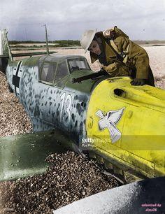 A British soldier inspects a crashed German Messerschmitt 109 on the beach