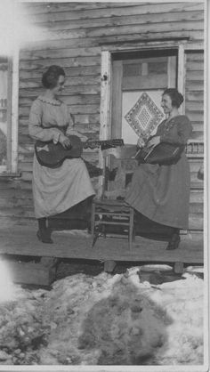 Two women, one playing guitar, the other, the zither | saskhistoryonline.ca