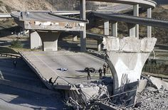 7 This January 17, 1994 photo shows the covered body of Los Angeles Police Officer Clarence Wayne Dean, 46, near his motorcycle which plunged off the State Highway 14 overpass that collapsed onto Interstate 5, an interchange that is now named in his memory. Dean was reporting to work in the predawn darkness and apparently never saw the collapsed bridge. (AP Photo/Doug Pizac)