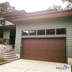 Shown here: An insulated, ribbed steel, faux wood door with a woodgrain finish and a mid century modern effect. Inside this garage there is a Hi-Lift track in order for the door to get up and over the transom windows. | Project and Photo Credits: ProLift Garage Doors of Haymarket Virginia | 'Why Homeowners Choose New Garage Doors That LOOK Like Wood' | ProLift Garage Doors of St. Louis Blog