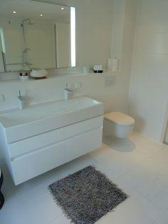 Elegant en strak wasbassin met gedurfde witte kranen. De spiegel met verlichting is in een totale nis geplaatst, zodat er ruimte ontstaat voor toiletartikelen.