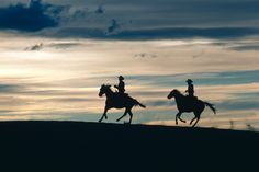 Two cowboys ride across a ridge at dusk in New Mexico. 1981. [1200  802]