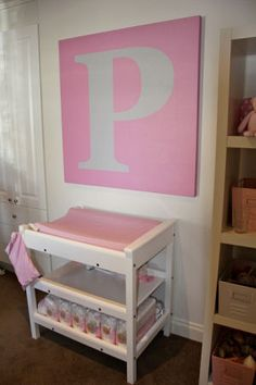 Large pink and white letter P painted wall canvas on a modern baby girl nursery wall