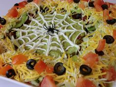 Layered taco dip is easy to make and is a great snack to serve at a party. This spooky version is perfect for Halloween!