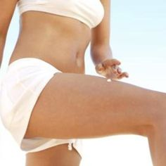 woman running lotion on thigh