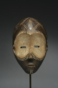 A Ngbaka or Ngbandi mask - A fine Ngbaka or Ngbandi mask Democratic Republic of Congo, the mask, with large ocular orbits completely covered with remains of white pigment; small wedge-shaped nose, high brow with classical scarification beneath a centrally parted coif, simplified ears and mouth, and a fine lustrous surface. height 11in