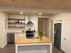 Small kitchen with a new life. Open shelves made from old barn planks and hung using iron pipe.