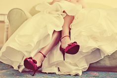 Non-traditional red shoes, under wedding gown.