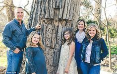 Annabel with her sisters and parents at the tree into which she fell - which they have now carved a Christian cross into