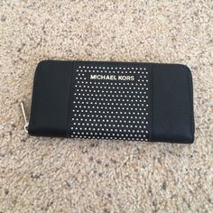 Michael Kors microstud stripe Wallet Has been used but in over all great condition. Has some spots on it that are pictured. It may wipe off. Lots of card holders and money slips inside. Zipper pocket in the middle. Michael Kors Bags Wallets
